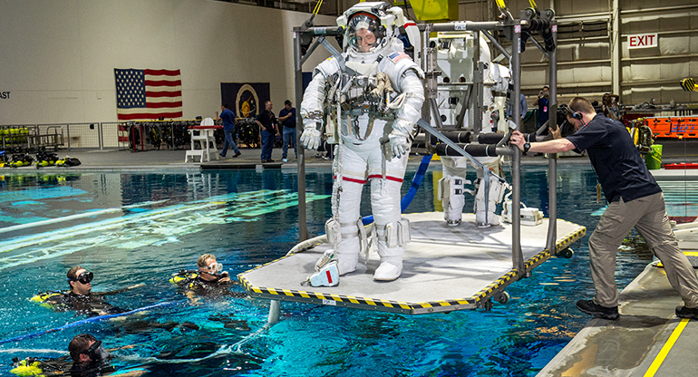 NASA astronauts are lowered into a pool containing a replica of the International Space Station at the Johnson Space Flight Center's Neutral  Buoyancy Laboratory for Extravehicular Activity training in Houston, Texas.