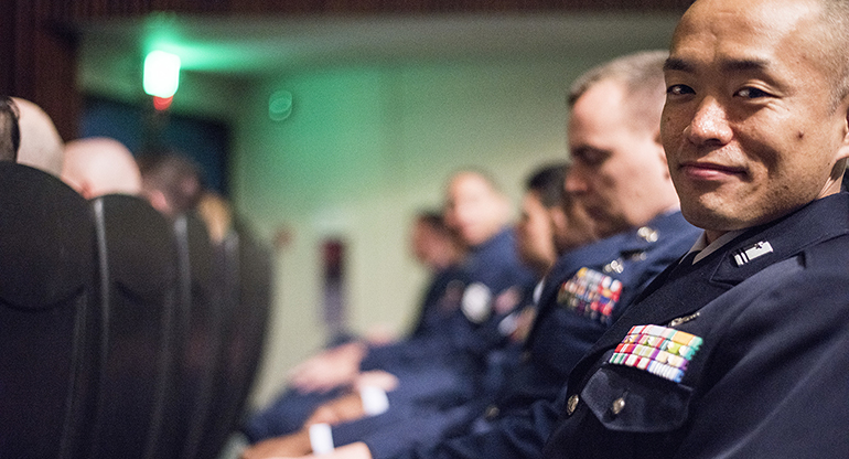 An Air Force officer sitting in a lecture looks over to the camera and smiles.
