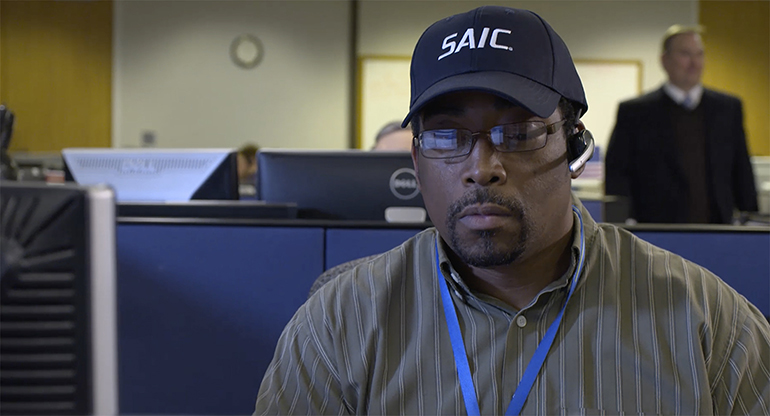 An SAIC employee talking on a headset, supporting customers