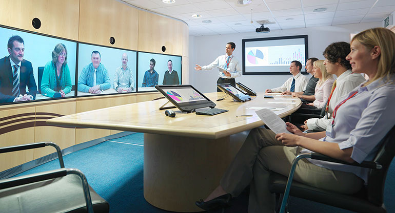 Business people in meeting room taking part in video conference
