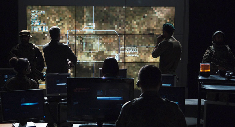 Group of military people in dark room watching the monitor