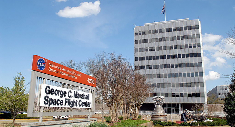 The George C. Marshall Flight Center building, seen from the front. The sign is on the left and the building is on the right.